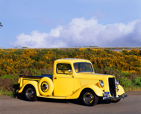 AUT 14 RK0099 04 © Kimball Stock 1936 Ford 327 Yellow Truck Side 3/4 View On Pavement By Hill Clouds Blue Sky