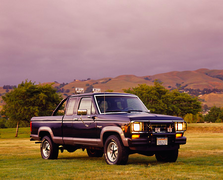 AUT 14 RK0128 01 © Kimball Stock 1987 Ford Ranger XLT Supercab 4x4 Truck Black Front 3/4 View On Grass