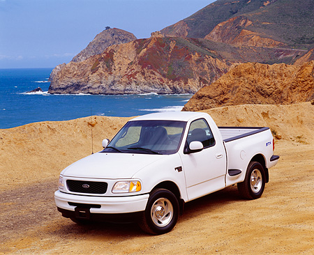 AUT 14 RK0155 08 © Kimball Stock 1998 Ford F150 XLT Truck White 3/4 Front View On Sand By Water And Rocks
