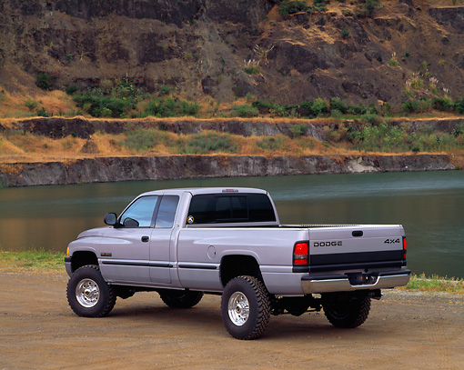 AUT 14 RK0182 02 © Kimball Stock 1999 Dodge Ram 2500 Truck Gray 3/4 Rear View On Dirt By Water