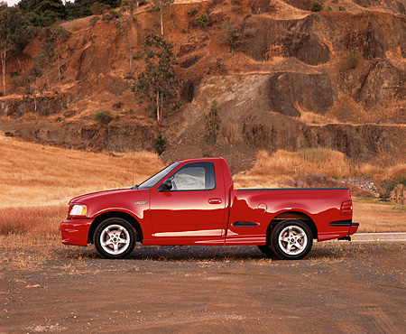 AUT 14 RK0204 02 © Kimball Stock 1999 Ford F150 Lightning Truck Red Profile On Pavement