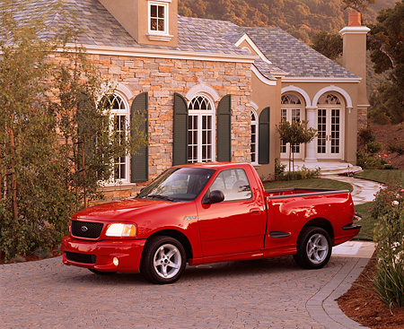 AUT 14 RK0211 01 © Kimball Stock 1999 Ford F150 Lightning Truck Red 3/4 Side View On Driveway By House