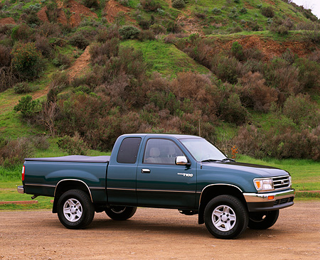AUT 14 RK0213 02 © Kimball Stock 1997 Toyota T-100 Truck Green 3/4 Side View On Dirt By Hill