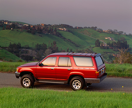 AUT 14 RK0238 03 © Kimball Stock 1992 Toyota 4 Runner Burgundy Profile On Pavement By Grass And Hills