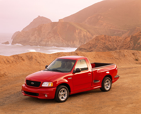 AUT 14 RK0255 01 © Kimball Stock 1999 Ford F150 Lightning Truck Red 3/4 Front View On Sand