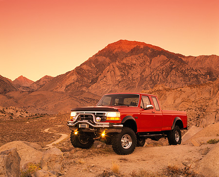 AUT 14 RK0273 01 © Kimball Stock 1995 Ford F250 4x4 Red 3/4 Front View On Dirt Headlights On Hills Background Red Sky At Dusk