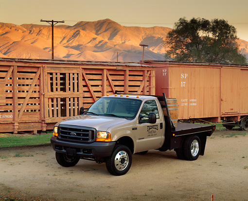 AUT 14 RK0285 03 © Kimball Stock 1999 Ford F550 Flatbed Champagne 3/4 Front View On Dirt By Train And Mountains