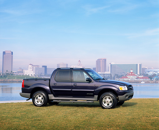 AUT 14 RK0348 03 © Kimball Stock 2001 Ford Explorer Sport Trac Blue 3/4 Front View On Grass By Water Buildings In Background Blue Sky