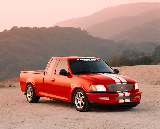 AUT 14 RK0369 04 © Kimball Stock 1997 Ford F-150 Thoroughbred With Cobra Engine Red 3/4 Front View On Dirt In Mountains