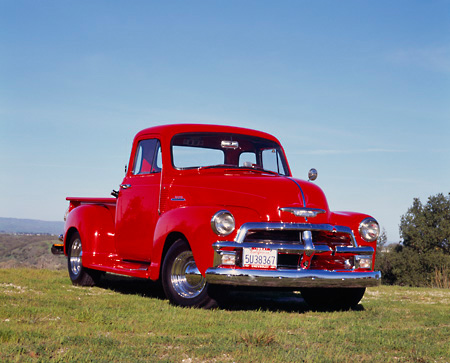 AUT 14 RK0387 03 © Kimball Stock 1954 Chevrolet 1/2 Ton Pickup Truck Red 3/4 Front View On Grass Blue Sky