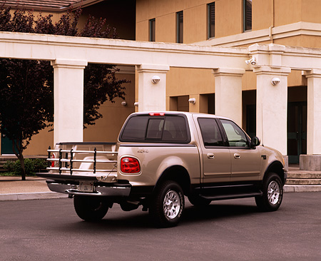 AUT 14 RK0406 02 © Kimball Stock 2001 Ford F150 Super Crew 4x4 Pickup Truck Gold 3/4 Rear View On Pavement By Building