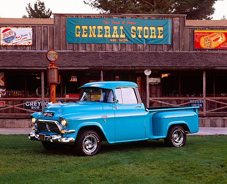 AUT 14 RK0426 02 © Kimball Stock 1957 GMC 100 Series 1/2 Ton Pickup Truck Turquoise 3/4 Side View On Grass By Store