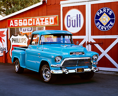 AUT 14 RK0432 02 © Kimball Stock 1957 GMC 100 Series 1/2 Ton Pickup Truck Turquiose 3/4 Front View On Pavement By Barn