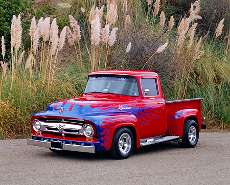 AUT 14 RK0451 02 © Kimball Stock 1956 Ford F100 Pickup Truck Red With Blue Flames Front 3/4 View On Pavement By Tall Bushes