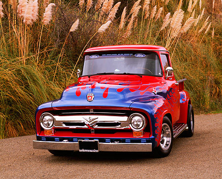AUT 14 RK0452 01 © Kimball Stock 1956 Ford F-100 Pick Up Truck Red With Blue Flames Front 3/4 View On Pavement By Tall Grass