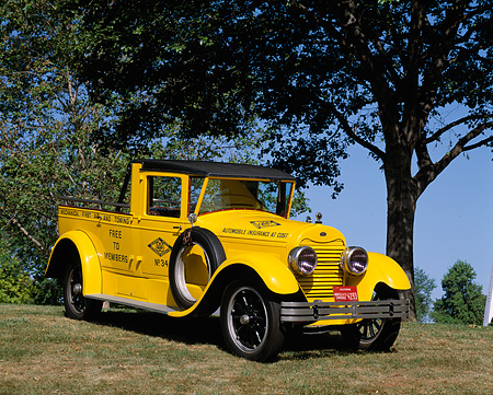 AUT 14 RK0515 03 © Kimball Stock 1922 Lincoln AAA Tow Truck Yellow 3/4 Front View On Grass By Trees