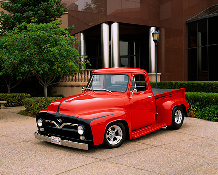 AUT 14 RK0519 04 © Kimball Stock 1955 Ford F-100 Custom Pick Up Truck Red 3/4 Front View On Pavement By Building And Trees