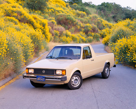 AUT 14 RK0523 06 © Kimball Stock 1982 VW Rabbit Pick Up Truck Beige 3/4 Front View On Pavement By Yellow Flower Bushes