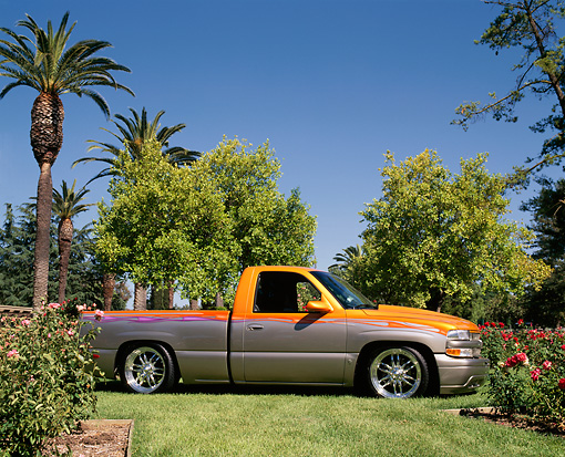 AUT 14 RK0539 03 © Kimball Stock 2000 Chevrolet Silverado Pick Up Orange And Silver 3/4 Front View On Grass By Trees Blue Sky