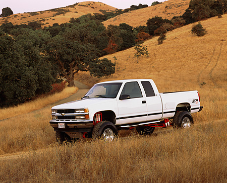 AUT 14 RK0588 02 © Kimball Stock 1996 Chevy Z71 Silverado White 3/4 Side View On Dry Grass Hill At Dusk