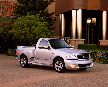 AUT 14 RK0630 04 © Kimball Stock 2001 Ford Lightning F-150 Silver 3/4 Side View On Pavement Building And Trees