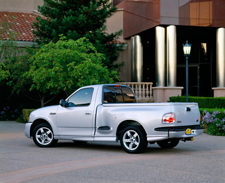 AUT 14 RK0632 01 © Kimball Stock 2001 Ford Lightning F-150 Silver 3/4 Rear View On Pavement By Building And Trees