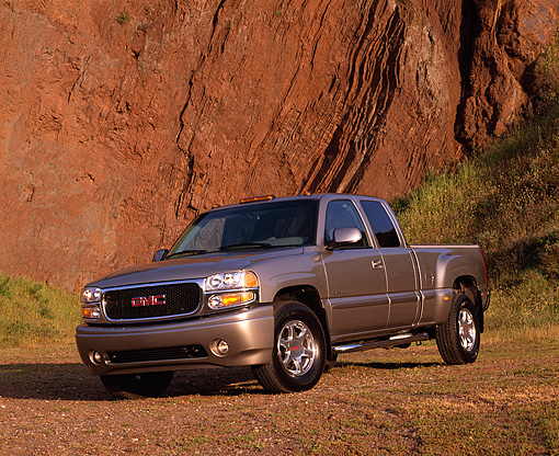 AUT 14 RK0665 02 © Kimball Stock 2002 GMC Sierra Denali AWD 4 Door Pewter 3/4 Front View On Dirt Against Rock