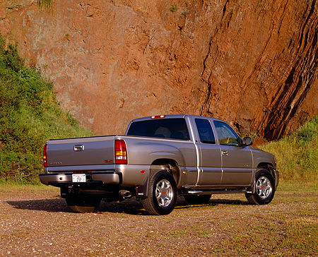 AUT 14 RK0668 03 © Kimball Stock 2002 GMC Sierra Denali AWD 4 Door Pewter Low 3/4 Rear View On Dirt Against Rock