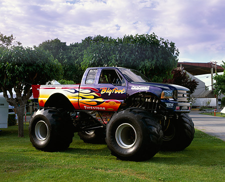 AUT 14 RK0735 09 © Kimball Stock Bigfoot Ford Monster Truck With Flames 3/4 Front View On Grass By Trees