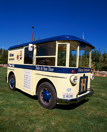 AUT 14 RK0781 07 © Kimball Stock 1931 Twin Coach Helms Bakery Truck Yellow And Blue 3/4 Front View On Grass Blue Sky