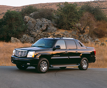 AUT 14 RK0789 01 © Kimball Stock 2003 Cadillac Escalade EXT Black 3/4 Side View On Pavement By Dry Grass And Rocks