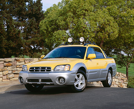 AUT 14 RK0795 01 © Kimball Stock 2003 Suburu Baja 4WD Yellow Front 3/4 View On Pavement By Trees