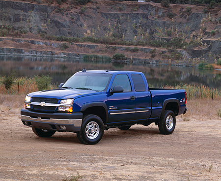 AUT 14 RK0804 03 © Kimball Stock 2003 Chevy Silverado LT 2500HD 4WD Extended Cab Blue 3/4 Front View On Dirt By Water