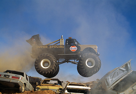AUT 14 RK0821 03 © Kimball Stock 1971 Chevrolet Monster Truck Gulf Oil Black And Gold Profile Airborne Over Crushed Cars
