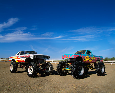 AUT 14 RK0834 09 © Kimball Stock Two Monster Trucks Trouble Maker And Wild Thing On Dirt Blue Sky