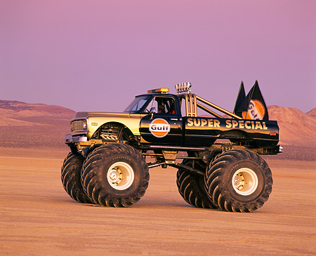 AUT 14 RK0851 03 © Kimball Stock 1971 Chevrolet Monster Truck Gulf Oil Black And Gold 3/4 Front View In Desert At Dusk