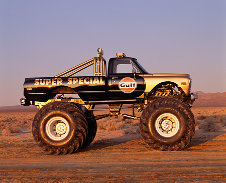 AUT 14 RK0852 09 © Kimball Stock 1971 Chevrolet Monster Truck Gulf Oil Black And Gold Profile View On Dirt Blue Sky