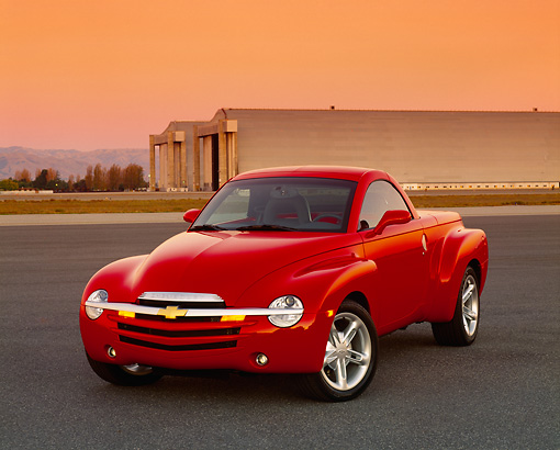 AUT 14 RK0964 02 © Kimball Stock 2003 Chevrolet SSR Convertible Red Truck 3/4 Front View On Pavement By Airplane Hanger Filtered