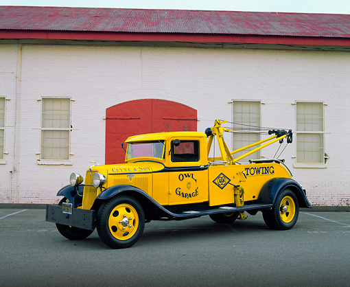 AUT 14 RK0972 03 © Kimball Stock 1934 Ford Tow Truck Yellow And Blue 3/4 Side View On Pavement By Building