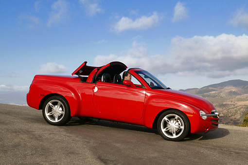 AUT 14 RK1035 01 © Kimball Stock 2004 Chevrolet SSR Convertible Truck Red 3/4 Side View On Pavement Hill