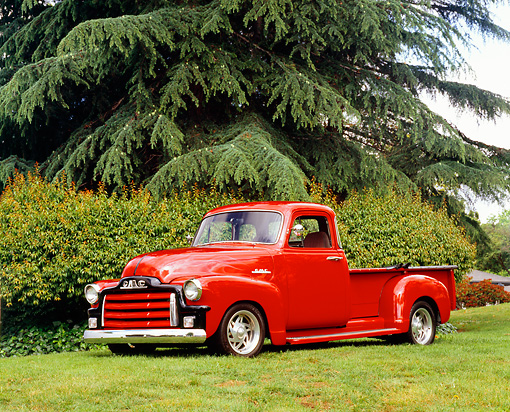 AUT 14 RK1061 03 © Kimball Stock 1955 GMC 100 1st Series Red Custom Pick Up Truck Red Side 3/4 View On Grass Trees Background