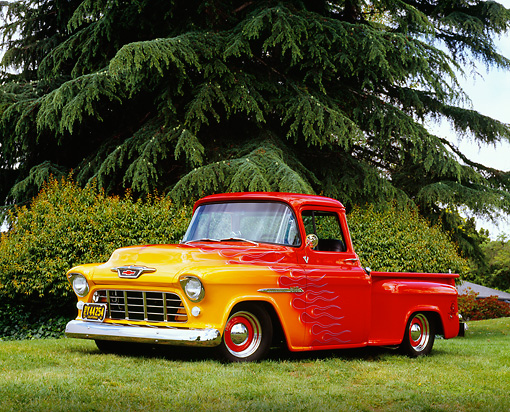 AUT 14 RK1074 04 © Kimball Stock 1955 Chevy 3100 1/2 Ton Pick Up Truck Red With Flames 3/4 Side View On Grass Trees Background