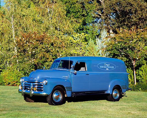AUT 14 RK1107 02 © Kimball Stock 1950 Chevy Panel 1 Ton Truck Blue 3/4 Side View On Grass By Trees