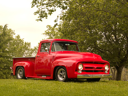 AUT 14 RK1145 01 © Kimball Stock 1956 Ford F-100 Pick Up Truck Red 3/4 Front View On Grass By Trees
