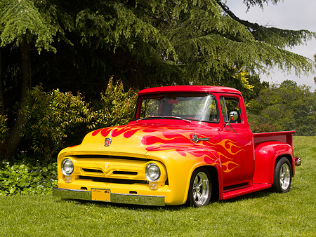 AUT 14 RK1150 01 © Kimball Stock 1956 Ford F-100 1/2 Ton Pick Up Truck Red With Flames 3/4 Front View On Grass By Trees