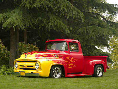 AUT 14 RK1152 01 © Kimball Stock 1956 Ford F-100 1/2 Ton Pick Up Truck Red With Flames 3/4 Side View On Grass By Trees