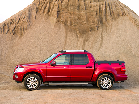 AUT 14 RK1180 01 © Kimball Stock 2007 Ford Explorer Sport Trac Pick Up Truck Red Profile Shot On Sand