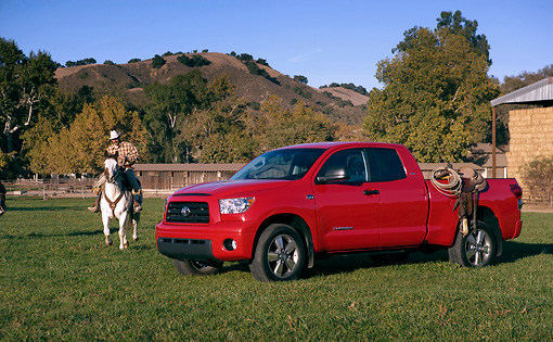 AUT 14 RK1264 01 © Kimball Stock 2007 Toyota Tundra Double Cab SR5 Red 3/4 Side View On Grass By Wrangler On Horse