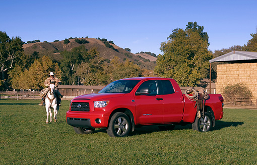 AUT 14 RK1265 01 © Kimball Stock 2007 Toyota Tundra Double Cab SR5 Red 3/4 Side View On Grass By Wrangler On Horse
