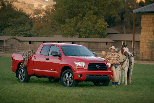 AUT 14 RK1268 03 © Kimball Stock 2007 Toyota Tundra Double Cab SR5 Red 3/4 Side View On Grass By Wrangler And Horse
